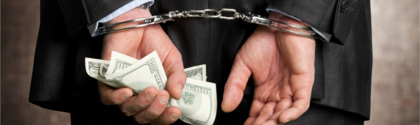 Man in business suit handcuffed while holding cash