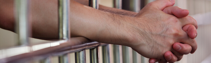 Close up photo of hands clasped together through jail cell bars