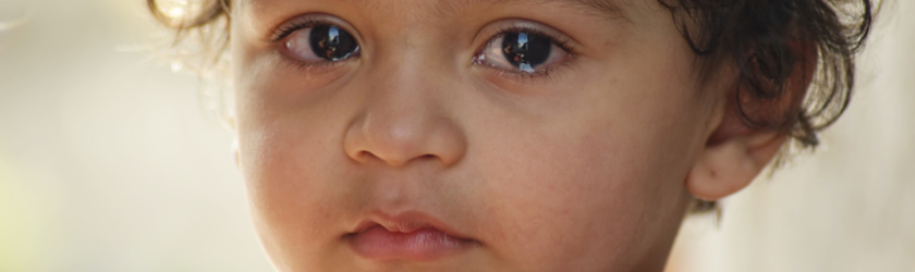 Close up portrait of a toddler looking at the camera with tears in its eyes