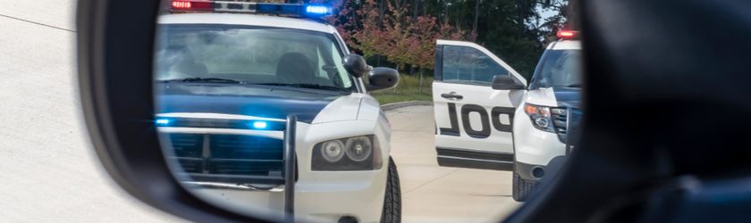 Two police cars are reflected in a car's driver side view mirror