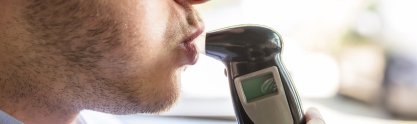 Closeup of a man blowing into a breathalyzer DWI test