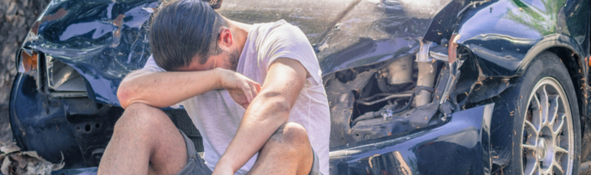 A man sits crying in front of his badly wrecked car