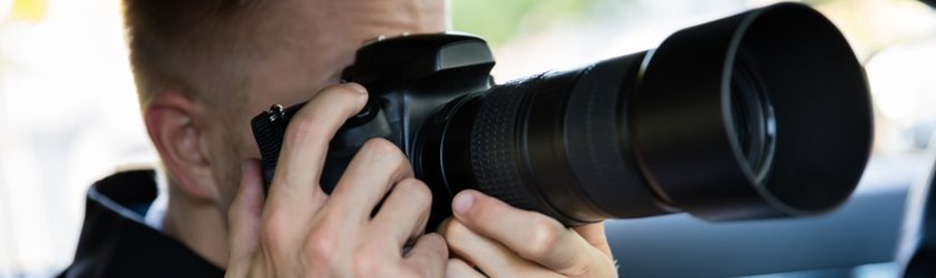Man takes a photo using a camera with a zoom lens