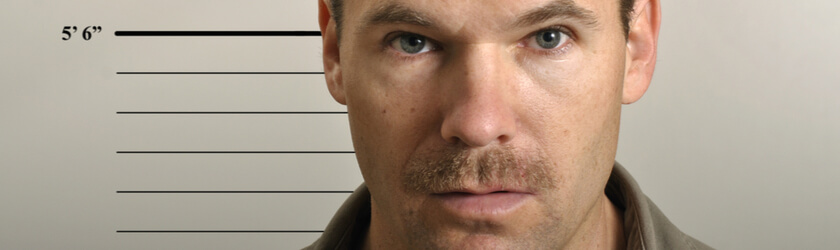 Close-up photo of a male suspect posing for a mugshot